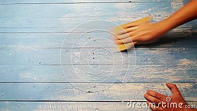 Ένα επιταχυνόμενο μήκος σε πόδηα ενός προσώπου που γυαλίζει τον ξύλινο πίνακα με το γυαλόχαρτο για φαίνεται παλαιότερο