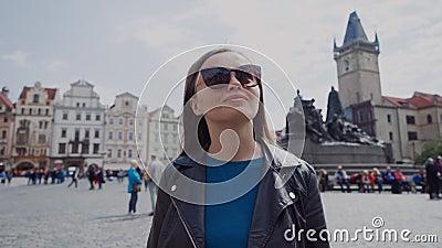 Ένα κομψό κορίτσι με γυαλιά ηλίου περπατά στην πλατεία Παλαιάς Πόλης στην Πράγα, Δημοκρατία της Τσεχίας Υπάρχει το μνημείο Jan Hu φιλμ μικρού μήκους