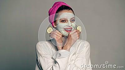 Ένα κορίτσι με μια μάσκα στο πρόσωπό της και μια πετσέτα στο κεφάλι της καλύπτει τα μάτια της με τα αγγούρια σε ένα γκρίζο υπόβαθ απόθεμα βίντεο