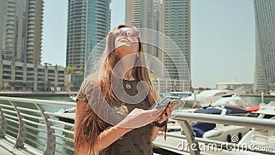 Ένα κορίτσι με τους μακρυμάλλεις πίνακες ένα μήνυμα στο smartphone στην αποβάθρα της μαρίνας του Ντουμπάι απόθεμα βίντεο