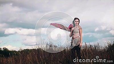 Ένα κορίτσι στέκεται σε ένα χωράφι στο φύλλωμα, φυσώντας τον άνεμο φιλμ μικρού μήκους