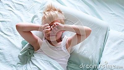 Ένα μικρό ξανθό αγόρι ξαπλώνει στο κρεβάτι και χαμογελά, το αγόρι τρίβει τα μάτια του με τα χέρια του νωρίς το πρωί Ώρα να ξυπνήσ απόθεμα βίντεο