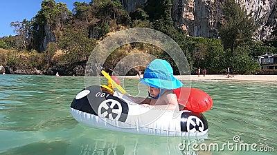 Ένα μικρό παιδί σε φουσκωτή βάρκα ή στρώμα με τη μορφή αυτοκινήτου κολυμπά σε μια τροπική αμμώδη παραλία Στο γαλάζιο πάναμ του μω απόθεμα βίντεο