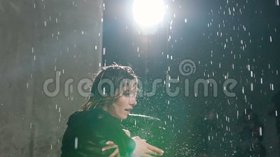 Ένα νέο καυκάσιο κορίτσι εκτελεί έναν σύγχρονο χορό χωρίς παπούτσια στο νερό κάτω από τις πτώσεις βροχής στο στούντιο χορός συναι φιλμ μικρού μήκους