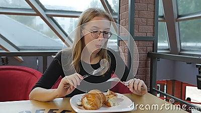 Ένα νέο κορίτσι με τα γυαλιά που κάθεται σε έναν καφέ που τρώει έναν croissant με ένα μαχαίρι και ένα δίκρανο φιλμ μικρού μήκους