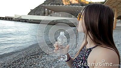 Ένα νέο κορίτσι στο ηλιοβασίλεμα κάθεται στην ακτή και πίνει το νερό καταστρέφει τα στοιχεία αισθάνεται το θερινό ύδωρ θάλασσας ι φιλμ μικρού μήκους