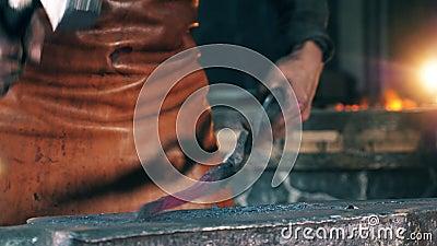 Ένα πρόσωπο χτυπά το αντικείμενο μετάλλων, διαμορφώνοντας το με ένα σφυρί σφυρηλατήστε απόθεμα βίντεο