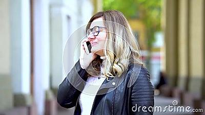 Ένα όμορφο κορίτσι με γυαλιά μιλάει στο smartphone απόθεμα βίντεο