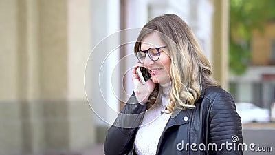 Ένα όμορφο κορίτσι με γυαλιά μιλάει στο smartphone φιλμ μικρού μήκους