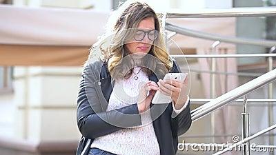 Ένα όμορφο κορίτσι με γυαλιά να στέκονται δίπλα στο ράφι με το smartphone και να δουλεύουν με αυτό Άνθρωποι της ομορφιάς φιλμ μικρού μήκους