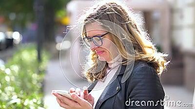 Ένα όμορφο κορίτσι με γυαλιά να στέκονται στο κρησφύγετο με smartphone, να χαμογελούν και να εργάζονται με αυτό Άνθρωποι της ομορ φιλμ μικρού μήκους
