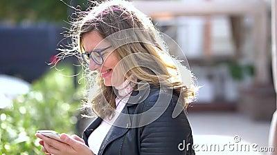 Ένα όμορφο κορίτσι με γυαλιά να στέκονται στο κρησφύγετο με smartphone, να χαμογελούν και να εργάζονται με αυτό Άνθρωποι της ομορ απόθεμα βίντεο
