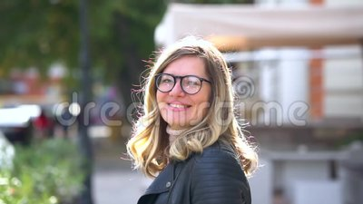 Ένα όμορφο κορίτσι με γυαλιά περπατάει κατά μήκος του κρησφύγετου κοντά Η γυναίκα γυρίζει και κοιτάζει και χαμογελά στην κάμερα απόθεμα βίντεο