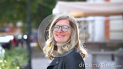 Ένα όμορφο κορίτσι με γυαλιά περπατάει κατά μήκος του κρησφύγετου κοντά Η γυναίκα γυρίζει και κοιτάζει και χαμογελά στην κάμερα Ό απόθεμα βίντεο