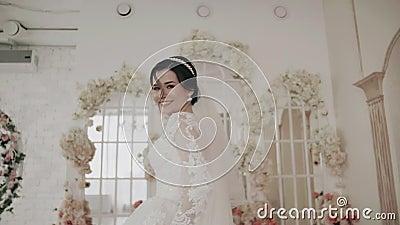 Ένα όμορφο κορίτσι με λευκό φόρεμα τρέχει μακριά από την κάμερα και χαμογελά απόθεμα βίντεο