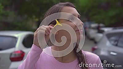 Ένα όμορφο κορίτσι με ένα ξίφος μυρίζει ένα κίτρινο λουλούδι και το βάζει πίσω από το αυτί της απόθεμα βίντεο