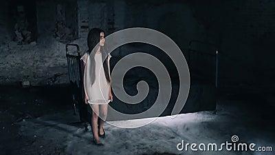 Ένα όμορφο νέο κορίτσι που περπατά σε μια σκοτεινή σπηλιά δωματίων Σκοτεινή ανασκόπηση κοινωνικό πρόγραμμα τρίχωμα μακρύ σκοτάδι  απόθεμα βίντεο
