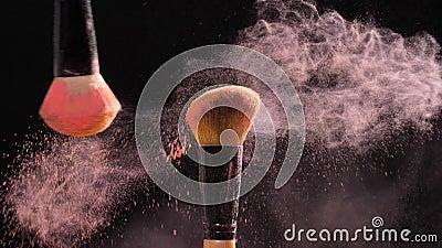 Έννοια των καλλυντικών και της ομορφιάς Βούρτσες σύνθεσης με τη ρόδινη έκρηξη σκονών στο μαύρο υπόβαθρο απόθεμα βίντεο