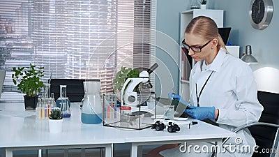 Έξυπνη χημικός επιστήμονας στο παλτό εργαστηρίου που γράφει τα αποτελέσματα του πειράματος απόθεμα βίντεο