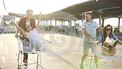 Αγόρια που ωθούν τα κάρρα αγορών με τα κορίτσια απόθεμα βίντεο