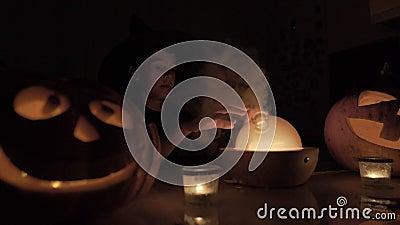 Αγόρι 9 ετών παίζει μάγο τις Απόκριες Με μια μαγική λάμπα και μια κολοκύθα στο τραπέζι τη νύχτα φιλμ μικρού μήκους