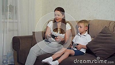 Αγόρι με τη συνεδρίαση μητέρων στον καναπέ και το παιχνίδι στο παιχνίδι δράσης στην τηλεόραση απόθεμα βίντεο