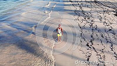 Αθλητικός άνδρας διασκεδάζει στην τροπική παραλία της Καραϊβικής Ωκεανός απόθεμα βίντεο