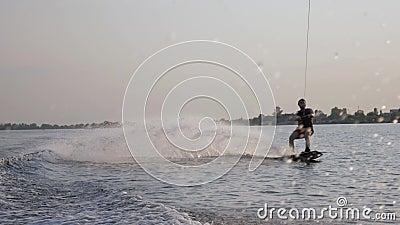 Αθλητικός άνδρας που εκπαιδεύεται στην αποβάθρα κατά μήκος του ποταμού πίσω από το μοτοποδήλατο και κρατά λαβή με σχοινί σε νερό  απόθεμα βίντεο