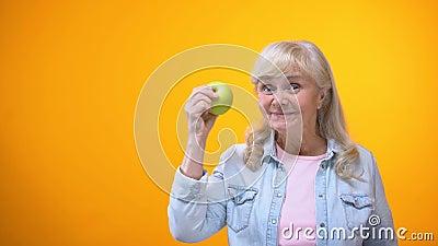 Αισιόδοξη ηλικιωμένη κυρία που δαγκώνει το φρέσκο πράσινο μήλο, υγιή δόντια, στοματολογία απόθεμα βίντεο