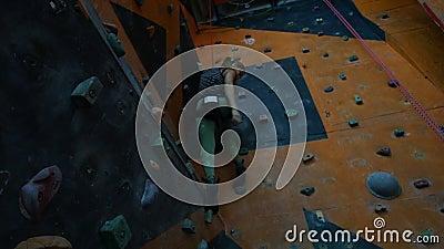 Ακραίος αθλητισμός Μια νέα γυναίκα που πηγαίνει κάτω από έναν δύσκολο τοίχο στο εσωτερικό απόθεμα βίντεο