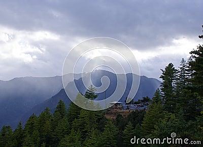 Ακτίνες του ελαφριού ραγίσματος ήλιων μέσω των σύννεφων επάνω στις αιχμές βουνών