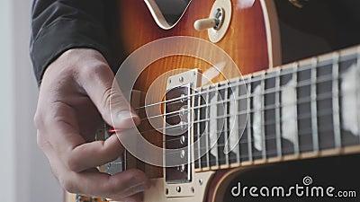 Ανδρικό χέρι με διαλέξιμο που παίζει ηλεκτρική επιλογή κιθάρας και στρουμισμό Χορδές αρσενικού χεριού και κιθάρας με πικουπ που π φιλμ μικρού μήκους