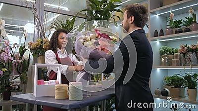 Ανθοκόμος που δίνει την έτοιμη floral δημιουργία στον πελάτη απόθεμα βίντεο