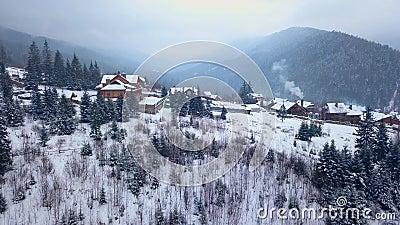 Αποκάλυψη της κεραίας της κατοικημένης τοποθεσίας στα βουνά στο χειμώνα Κτήρια ορεινών χωριών στις χιονώδεις κλίσεις λόφων απόθεμα βίντεο