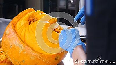 Αποκριάτικη προετοιμασία κατασκευή γρύλου Μάτια χειρός, μύτη και χαμόγελο με μαχαίρι στην πορτοκαλί κολοκύθα Κλείσιμο φιλμ μικρού μήκους