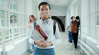 Αργή κίνηση μιας αρκετά αφρικανίδας Αμερικανίδας που στέκεται στο σχολικό διάδρομο με βιβλία φιλμ μικρού μήκους