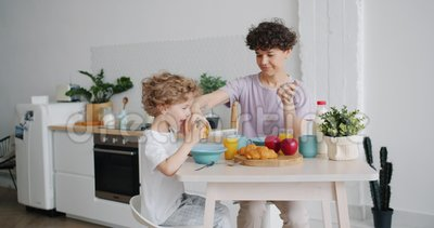 Αργή κίνηση της μητέρας που βάζει δημητριακά στο πιάτο για μικρό γιο στην κουζίνα του σπιτιού φιλμ μικρού μήκους
