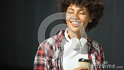 Αρκετά αφροαμερικανός θηλυκό τσάι κατανάλωσης υπαίθριο και απόλαυση του ευχάριστου καιρού απόθεμα βίντεο