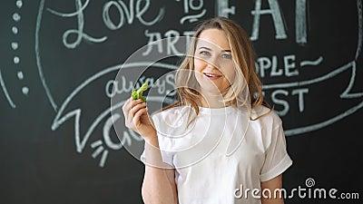 Αρκετά εύθυμη νέα τοποθέτηση γυναικών με τα φρέσκα πράσινα φύλλα μαρουλιού κατανάλωση έννοιας υγιής dieting απόθεμα βίντεο