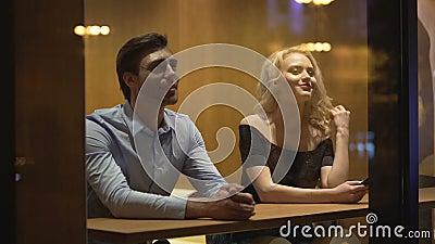 Αρκετά θηλυκό φλερτ με το νεαρό άνδρα στον καφέ, που εξισώνει το χρόνο, την επανάληψη και την ημερομηνία απόθεμα βίντεο