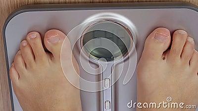 Αρσενικά ή θηλυκά πόδια που ζυγίζουν στην ηλεκτρονική κλίμακα με τη μεγέθυνση στην επίδειξη φιλμ μικρού μήκους