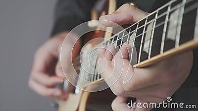 Αρσενικά χέρια που παίζουν ηλεκτρική κιθάρα κοντά Δάκτυλα στο χαρτόνι κιθάρας που κρατά το κομοδίνο και παίζει χορδές και σόλο Μο απόθεμα βίντεο