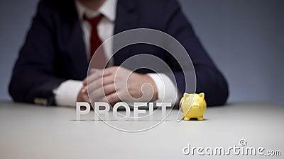 Αρσενικό χέρι που βάζει το νόμισμα στο κιβώτιο χρημάτων χοίρων Κέρδος συσσώρευσης στη σύγχρονη επιχείρηση φιλμ μικρού μήκους