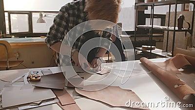 Αρσενικό χειροτεχνικό περπάτημα στην κατασκευή του εργαστηρίου, craftswoman τέμνον δέρμα στα κομμάτια για τα χειροποίητα αγαθά σε απόθεμα βίντεο