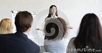 Ασιατικός ομιλητής επιχειρηματιών στην παρουσίαση με την ομάδα επιχειρηματιών που υποβάλλουν τις ερωτήσεις κατά τη διάρκεια της σ φιλμ μικρού μήκους