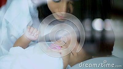 Ασιατικός ύπνος μωρού και φιλί στο μέτωπο για τη νεαρή μητέρα φιλμ μικρού μήκους