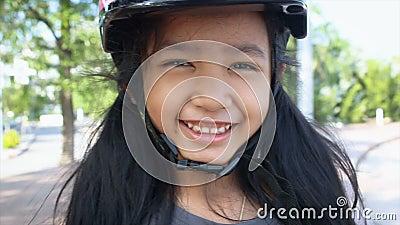 Ασιατικό χαμόγελο μικρών κοριτσιών με την ευτυχία που φορά το κράνος αθλητικής ασφάλειας απόθεμα βίντεο