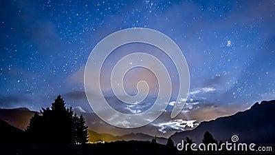 Αστέρια και φεγγάρι νυχτερινού ουρανού Timelapse στα γρήγορα σύννεφα με το υπόβαθρο βουνών απόθεμα βίντεο