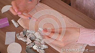 Αφαίρεση του πηκτώματος στίλβωση από τα καρφιά Η γυναίκα βγάζει το φύλλο αλουμινίου από τα δάχτυλά της Και αφαιρέστε shellac από  απόθεμα βίντεο
