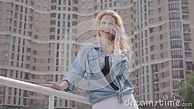 Βέβαια χαμογελώντας ξανθή γυναίκα στο σακάκι τζιν που μιλά από το κινητό τηλέφωνο μπροστά από τον ουρανοξύστη lifestyle urban Θηλ φιλμ μικρού μήκους